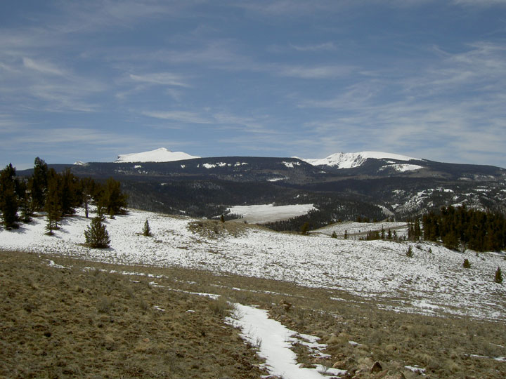 An open meadow partially covered in snow, leading down to forested hills in the distance, backed by snow covered peaks.