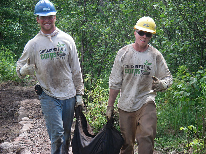 Dirty Conservation Corps workers haul a bag along a trail.
