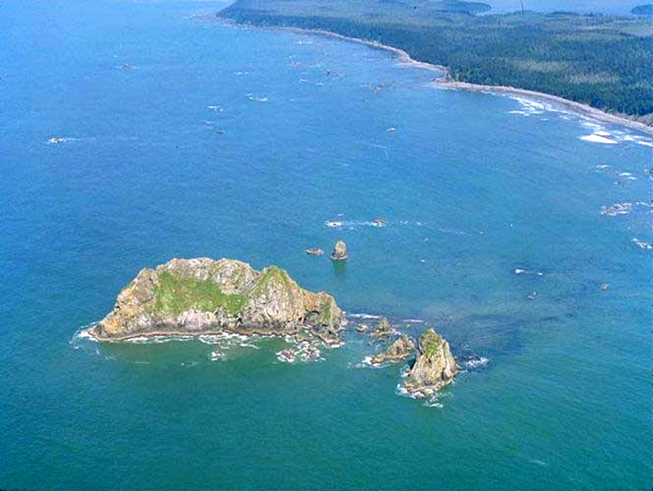 An aerial view of a small rocky island, jutting out of the shallow blue water near the coast.
