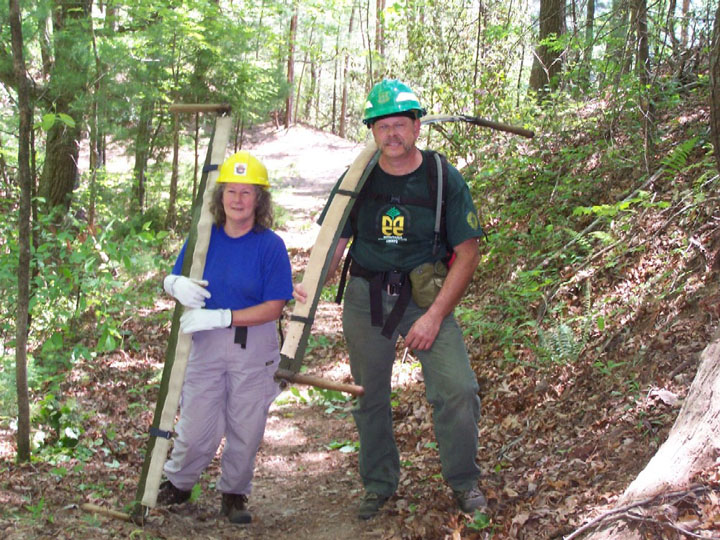 A man and a woman posing on a forest trail, each holding large hand saws.