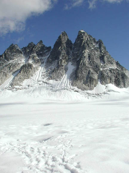 A view of a rock hill/mountain from the Pika Glacier. There are footprints in the snow and the sky is clear.