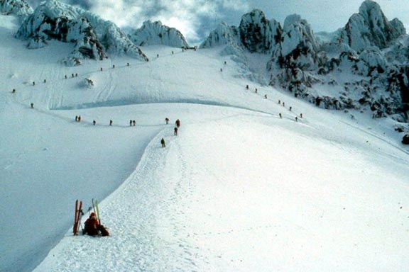 A snow covered ridge dotted with climbers, sweeping away to massive rocky pinnacles above.