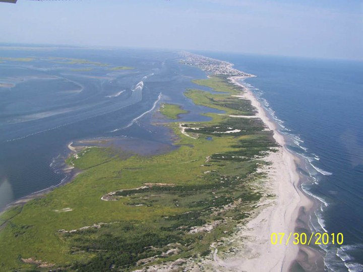 Ocean waves lap against an Island with a sandy beach on one side and lush green vegetation on the other with a beach community toward the end.