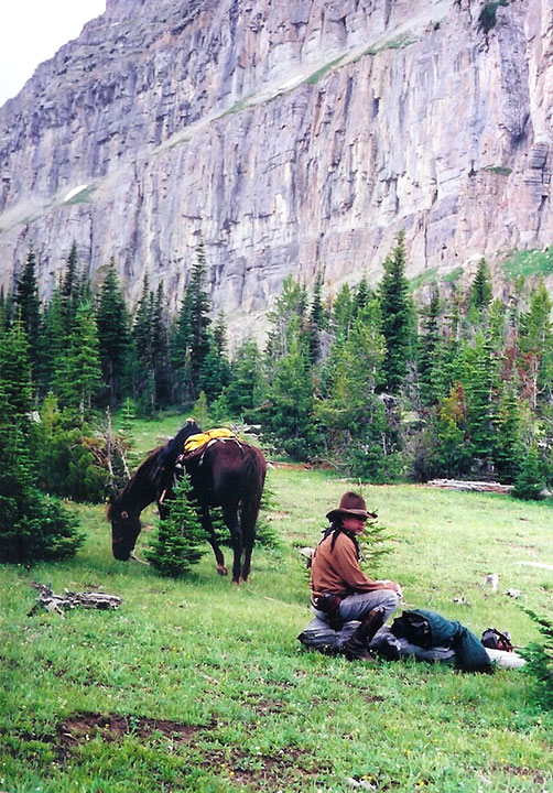 A rider sits next to a horse at the base of a rocky cliff.