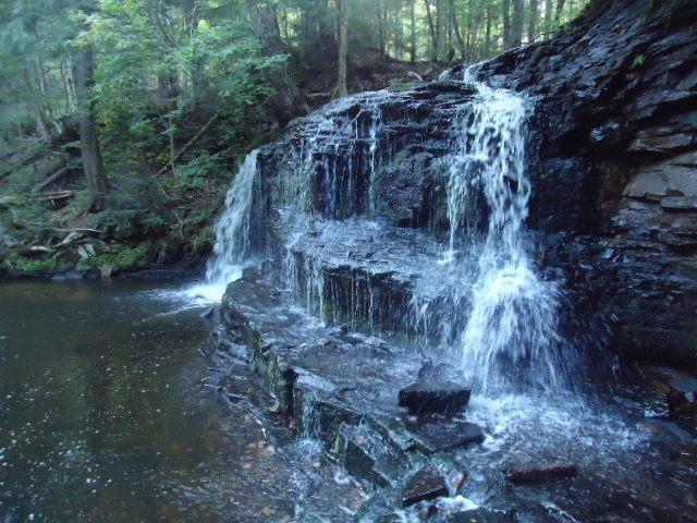 A waterfall cascades into a deep blue pool.