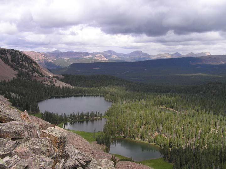 A rocky ridge is bordered below by three small lakes, surrounded by dense green forest, which stretches away across the valley, under stormy clouds.