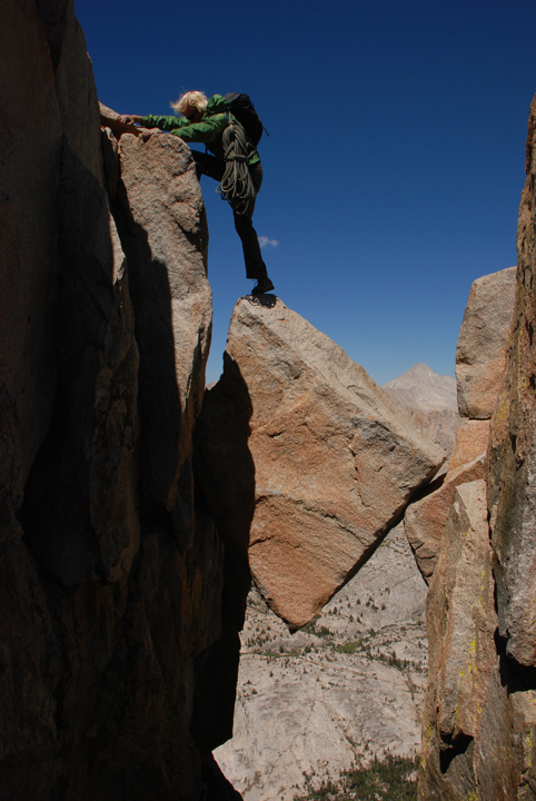 A rock climber scales a precarious area where a square shaped rock that is wedged between two rock walls, high above the ground.