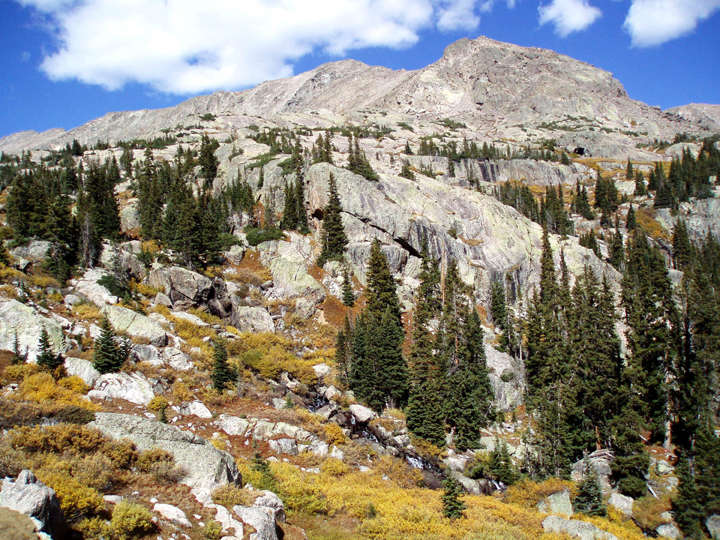 A steep rocky slope covered by shrubs and alpine trees leads up to large rocky mountain peaks.