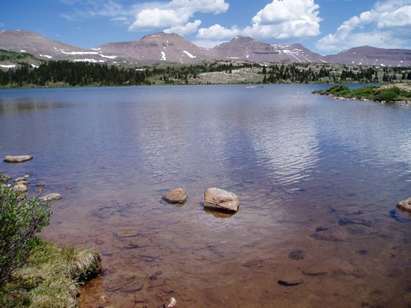 Blue sky and white clouds reflecting from the glassy surface of an alpine lake, with low mountains laced with snow rising above the forest beyond.