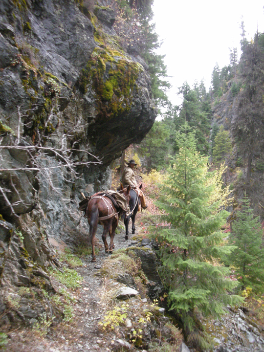 A man riding a horse leads another along a skinny trail on a steep rocky slope.