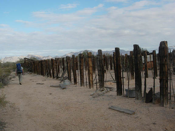 Remains of the old stockyard at Monreal Well. The stockyard consists of large wood fence posts and wire fencing. The area is littered with discarded items from the stockyard and a backpacker walks along the fence.