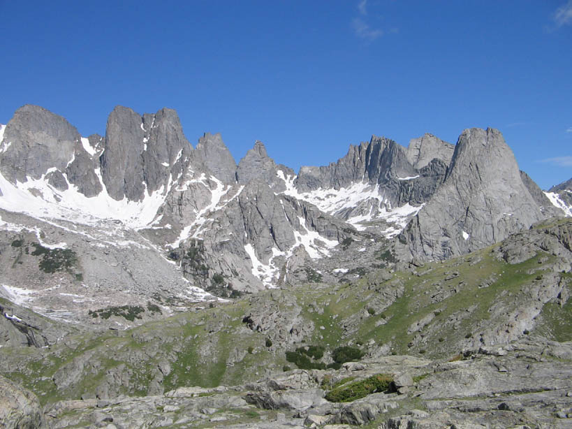 A rugged alpine scene, a myriad of jagged rocky peaks laced with snow rising towards an empty blue sky.