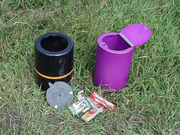 This photo depicts two different types of food canisters. One a black with a detachable lid and one is purple with a hinged lid.