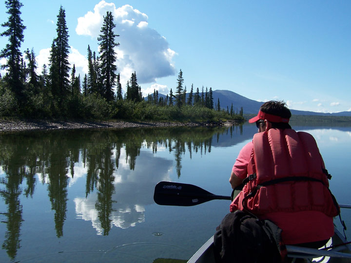 A lone canoer in a bright red vest, rests his paddle and looks out at the reflection of the trees and blue sky on the mirror surface of the lake.