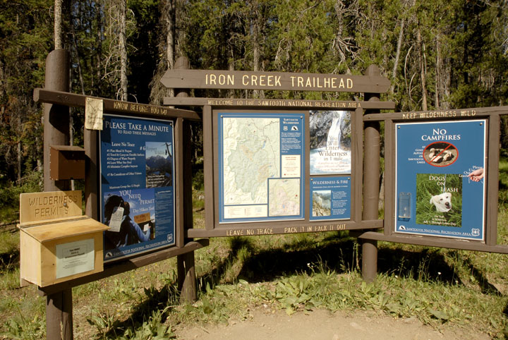 A large trailhead sign and interpretive boards on the edge of the forest next to a trail.