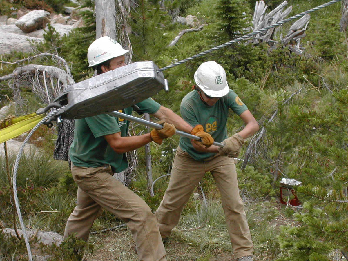 Two workers in green shirts and hard hats, working to winch a large block connected to a cable.