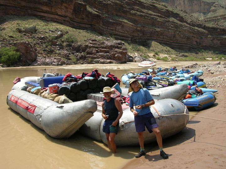 Rafters lightheartedly pose for the camera in front of their gear in Grand Canyon National Park.