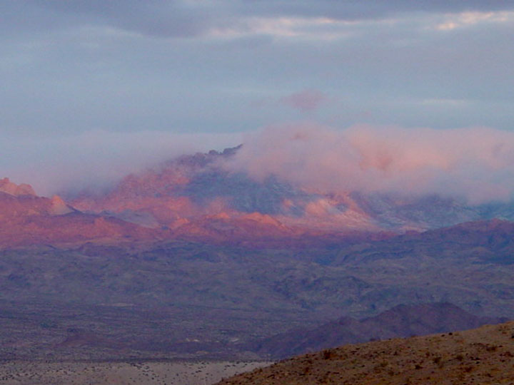 Partially shrouded in snow and cloud, distant mountains rise above the desert landscape bathed in the pink and purple hues of alpenglow.
