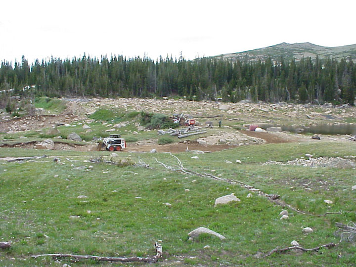 A rocky meadow bordered by dense forest, two small pieces of equipment work to clear an old pile of rubble from along the edge of a small lake.