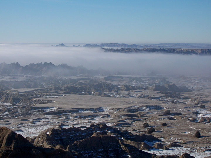 A look out over a rugged plain of rocky pinnacles and ravines, patches of snow and fog obscuring part of view.