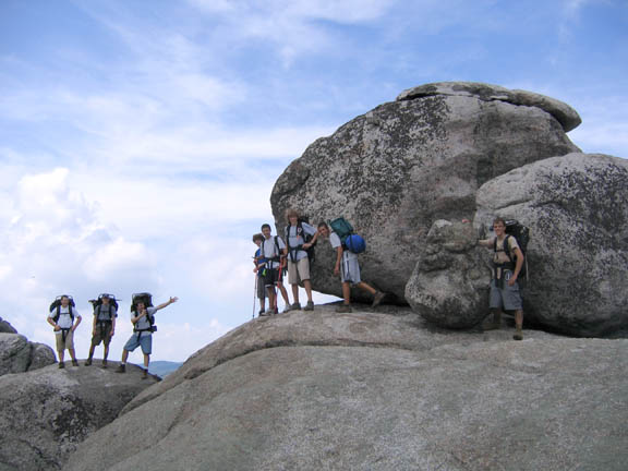 Backpackers pose next to huge boulders on a partly cloudy day at old