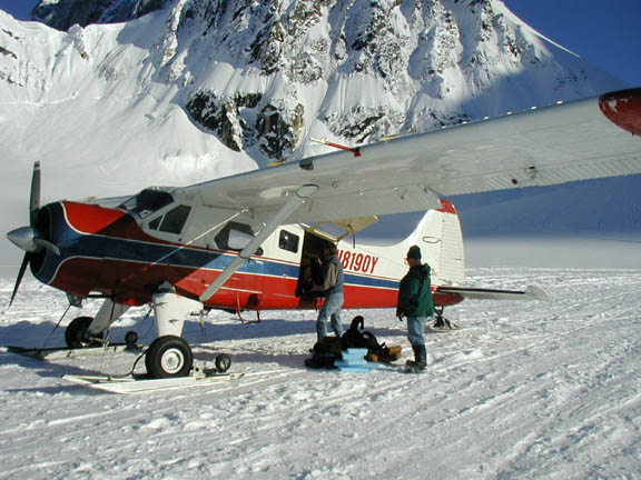 On a glacier in Alaska's Ruth Amphitheater, two men unload gear from a small bush plane.