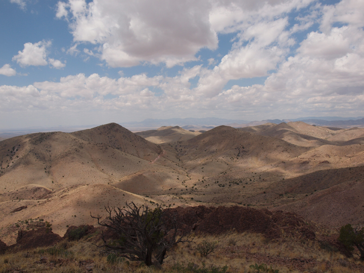 Large white clouds cast shadows down onto endless desert hills.