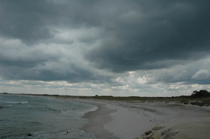 Ocean waves wash up over a sandy beach while dark storm clouds form overhead.