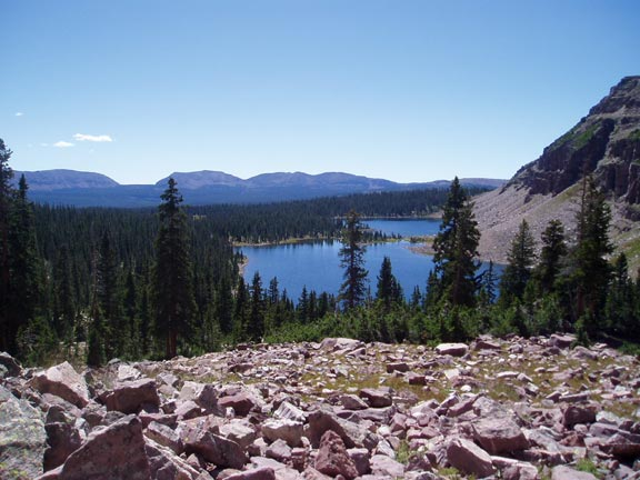 Looking down a rocky slope to dense forest below, surrounding a small lake at the base of a rocky face.