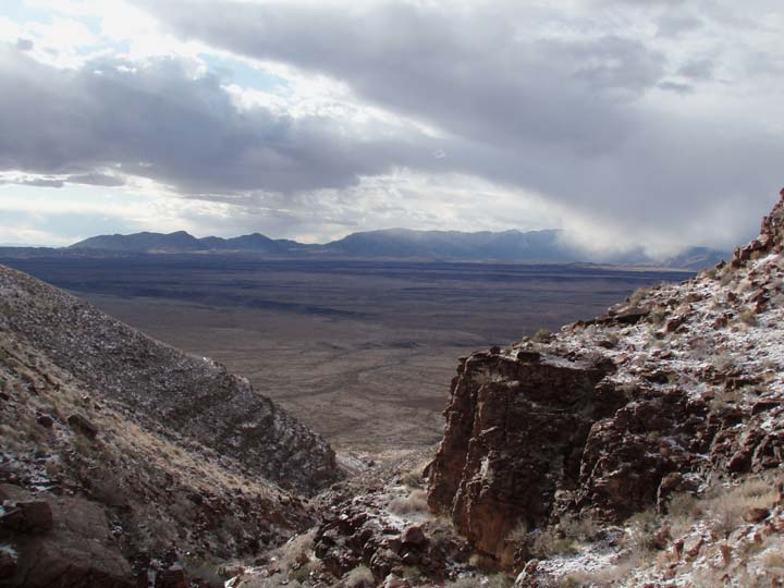 Looking down a jagged desert wash to an open valley below, stretching away to distant mountains, under a stormy sky.