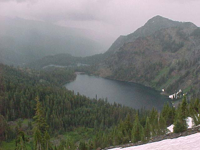 This snapshot depicts a lake nestled at the base of a mountainous area. Clouds hang around the tops of the hills and mountains and it appears to be raining, lightly. Snow lingers in patches on the hillsides, where coniferous grow in large numbers.