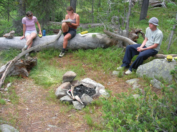 Three volunteers sit on fallen trees around a campfire pit during the day. This photo was taken during University of Montana summer 2007 volunteer weed inventory study.