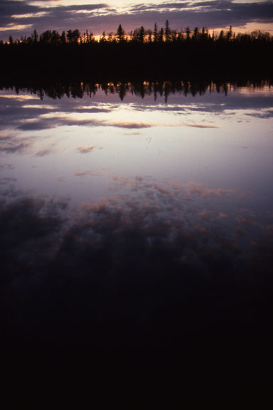 Sunset casts pinks and purples across the sky and creates reflections of the sky of the still water of the Kawishiwi.