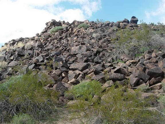 A hill covered in rocks and dotted with shrubs.