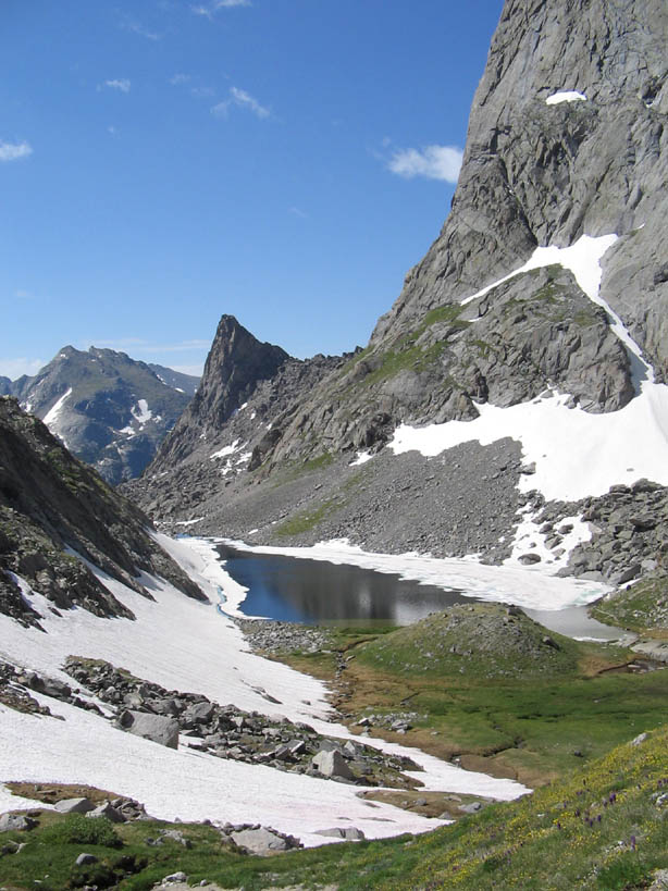 A massive rock wall rising from the edge of a small alpine pond, surrounded by green grass and patches of snow.