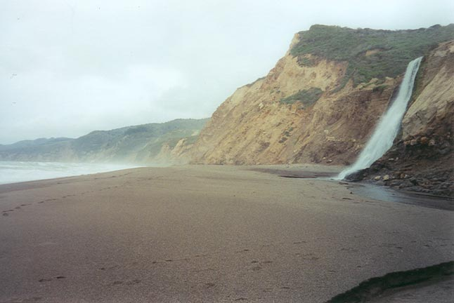 A large waterfall pouring over the edge of a high coastal cliff face, to the sandy brown beach below.