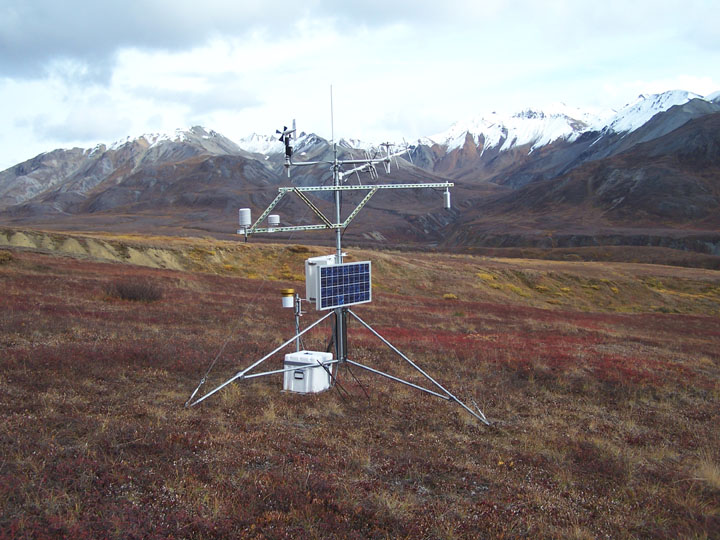 A small scientific station standing on the open tundra, massive snow-capped peaks rising in the background.
