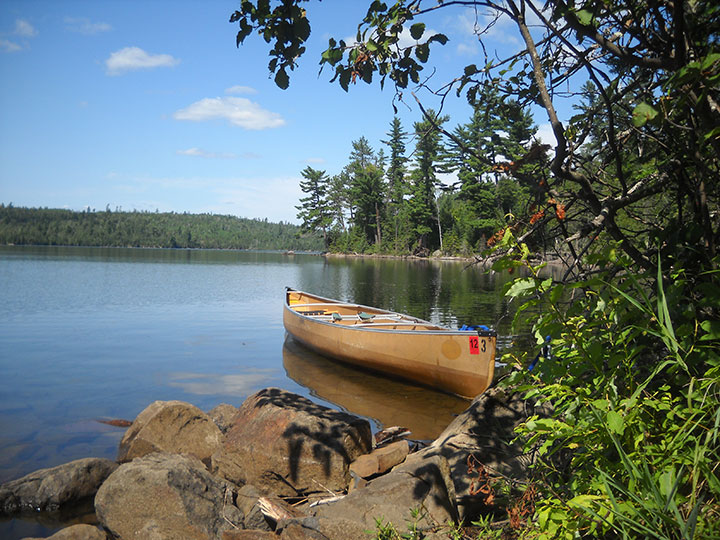 A canoe sits at the end of a lake.