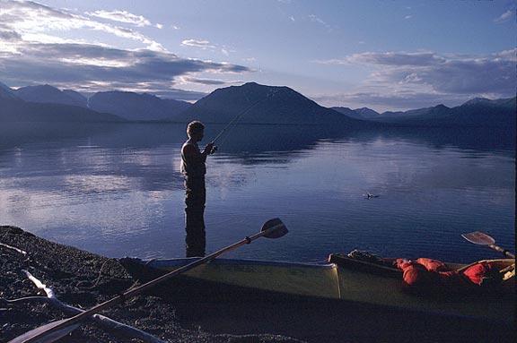 A Kayaker fishing from the shore of the Kenai Peninsula at dusk.
