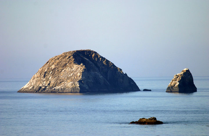 Several small rock islands jut out of the water bathed in evening light, behind them water and sky blend into an almost seamless blue background.
