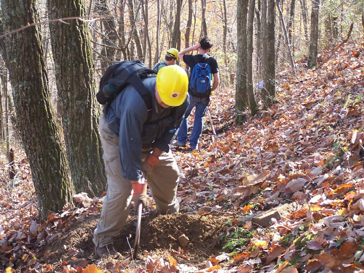 A man digging a rock out of the trail with a pick axe.