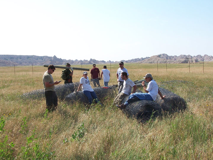 A small group of workers standing in the prairie grass near several large rolls of fencing.