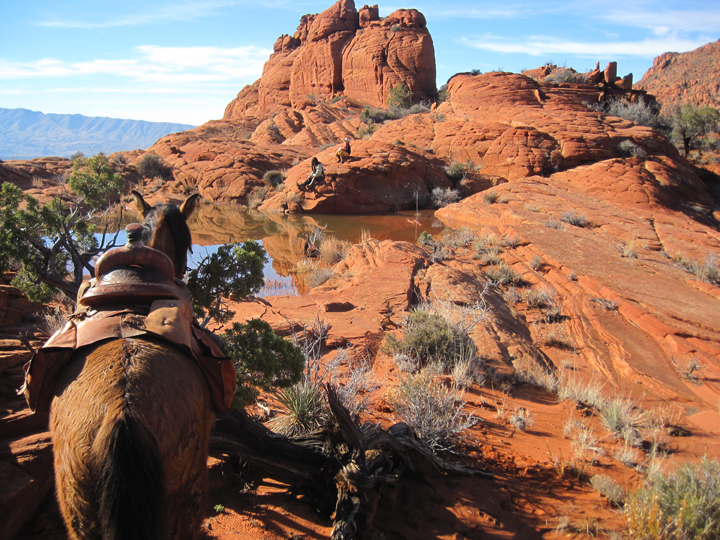 Two people sit beside a pool of water caught between large smooth red rocks.