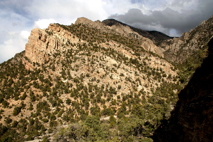 High cliffs protruding from a tall desert hill, freckled with green brush.