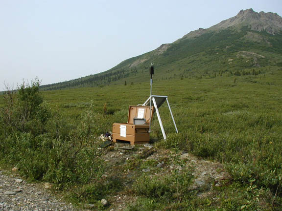Sound monitoring equipment is set up near the Savage River. In the distance is a hill covered in green grass.