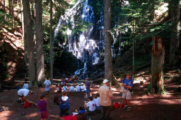 A group of young hikers gathered in the open forest, at the base of a small horsetail waterfall.