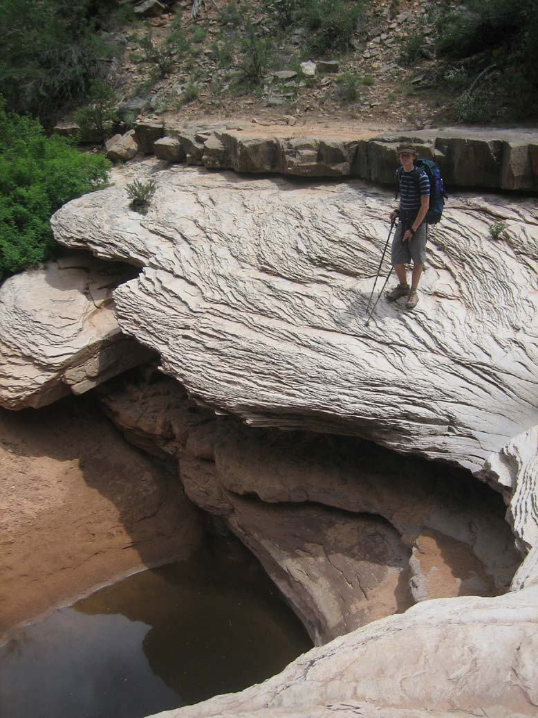 A lone hiker standing on the edge of a large slab of rock, above a deep pool of water below.