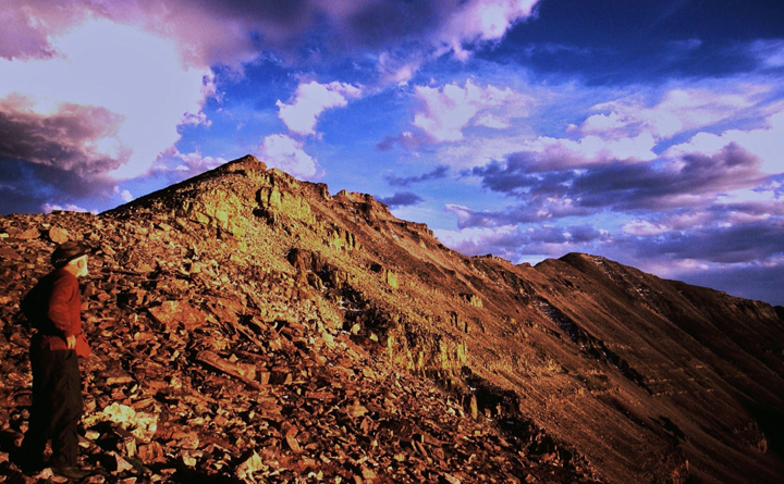 A mountain peak turned gold by the shimmering light of the setting sun with parted clouds overtop as a hiker glances up at the last stretch to the top.