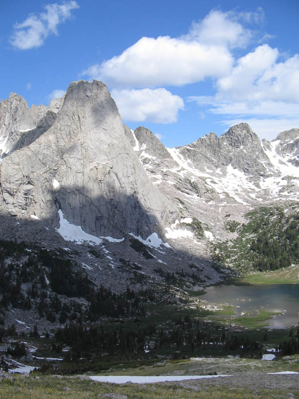 Jagged scaly gray peaks stand high over a small lake, surrounded by sparse alpine forest and patches of snow.