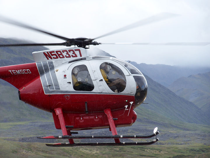 A close-up of a small red and white helicopter, flying low over the arctic tundra.